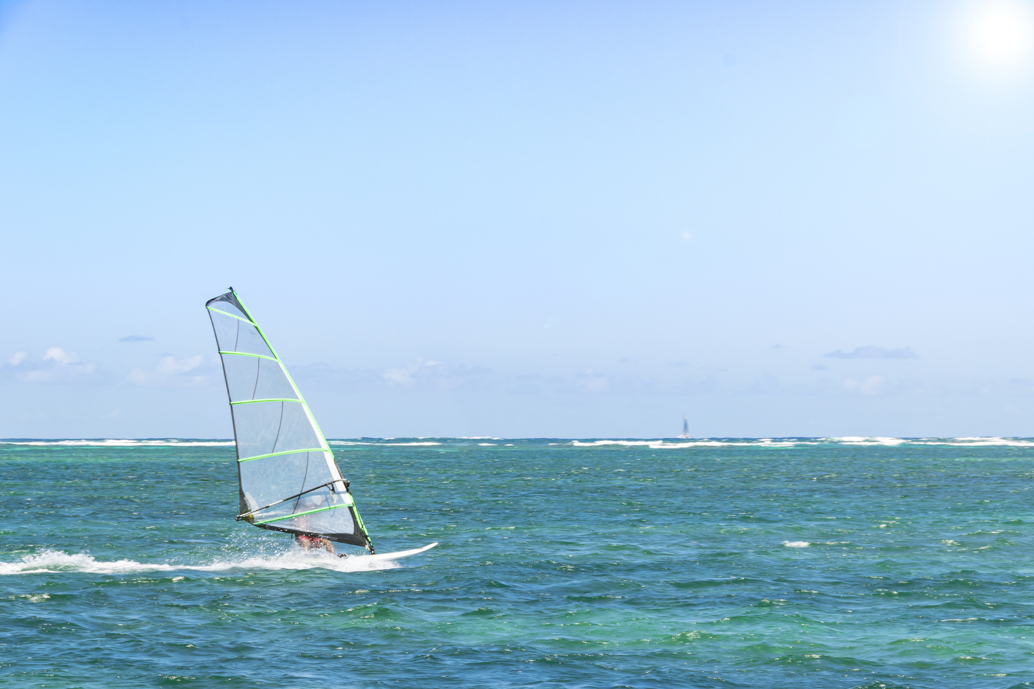 Windsurfing. Windsurfer Surfing The Wind On Waves In Ocean, Sea. Extreme Sport Action. Recreational Sporting Activity. Healthy Active Lifestyle